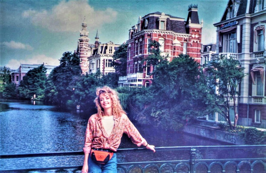 me standing in the sun leaning on a bridge over the canal in Amsterdam